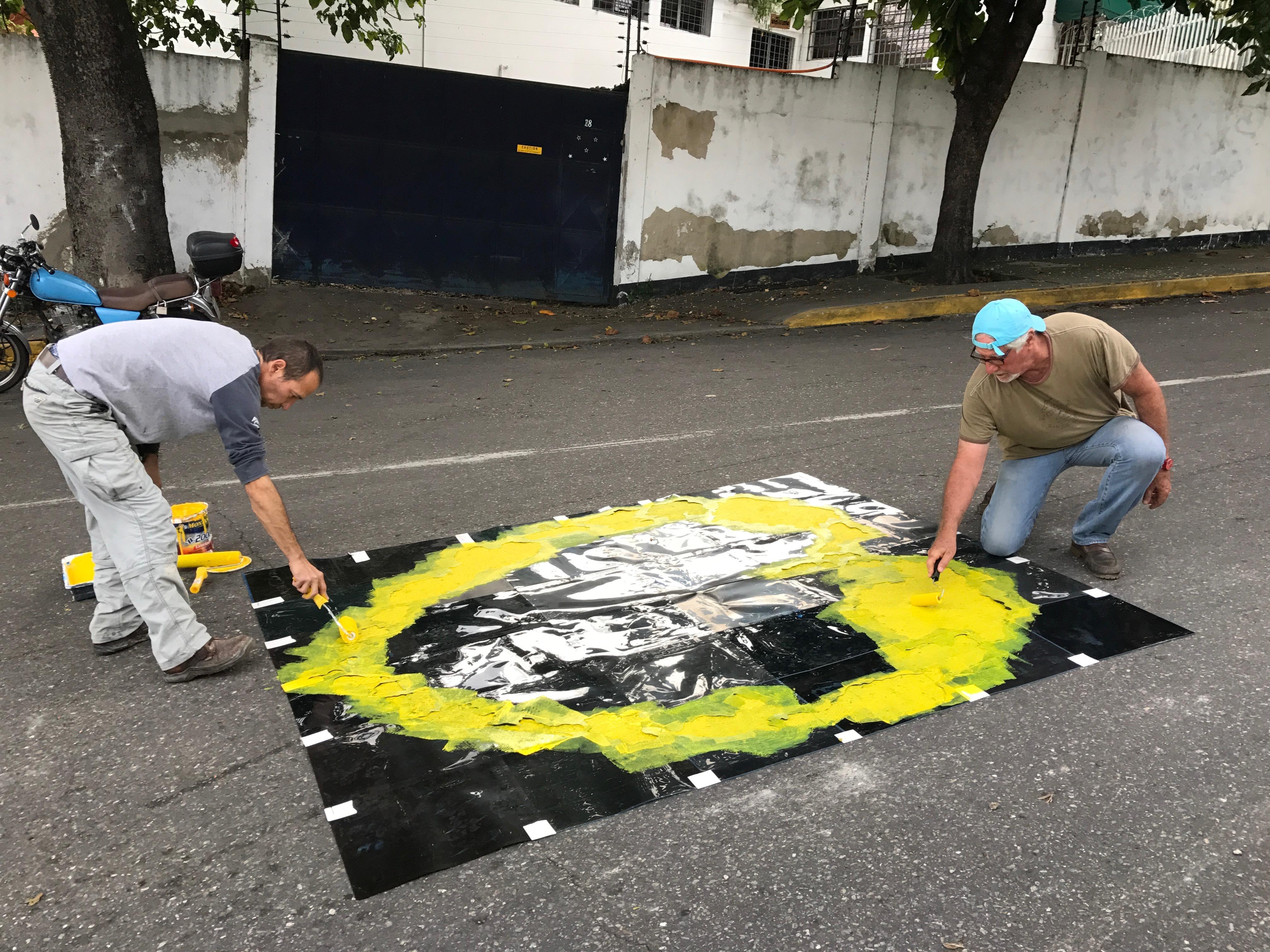 Ricardo Benaim en la calle frente a la Quinta Papeles, pintando un stencil en el asfalto